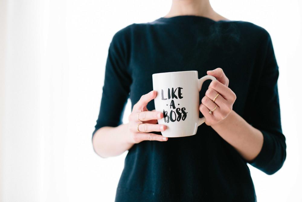 "Woman holding a mug reading ""Like a bos"""